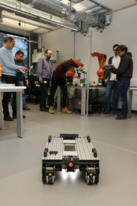 "FHWS - The robotics team in the laboratory. In the foreground an autonomous mobile robot that is used as an ""automated guided vehicle"" (AGV) for logistic tasks."